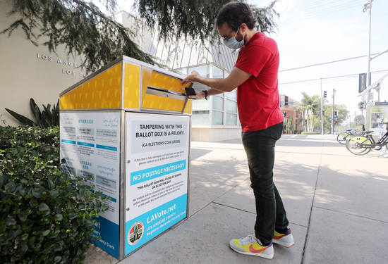 LOS ANGELES, CALIFORNIA - OCTOBER 05: Voter Cody Crump places his ballot in a mail-in ballot drop box outside of a library ahead of Election Day on October 5, 2020 in Los Angeles, California. Early voting has begun in California with Los Angeles County posting 400 secure vote-by-mail drop boxes across the county. (Photo by Mario Tama/Getty Images)