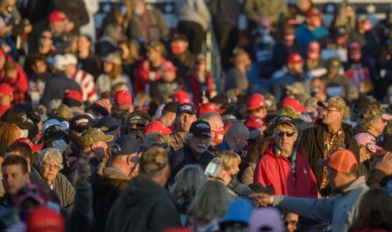 """JOHNSTOWN, PA - OCTOBER 13: Supporters of President Donald Trump await his arrival for a rally at the John Murtha Johnstown-Cambria County Airport on October 13, 2020 in Johnstown, Pennsylvania. White House physician Dr. Sean Conley declared on Saturday that the president is """"no longer considered a transmission risk to others,"""" while those in attendance had their temperature checked and masks were said to be required.  (Photo by Jeff Swensen/Getty Images)"""