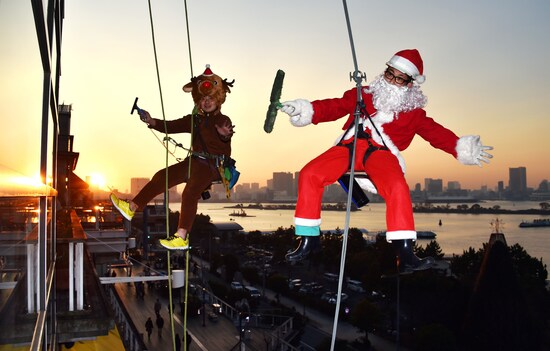 Workers in Santa Claus (R) and reindeer costumes (L) clean the windows in front of a shopping mall on Tokyo's waterfront on December 24, 2014. The costumes were worn as part of a Christmas campaign to attract buyers. AFP PHOTO / Yoshikazu TSUNO (Photo credit should be YOSHIKAZU TSUNO / AFP via Getty Images)