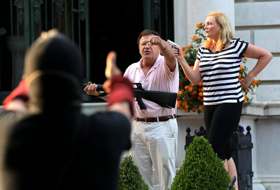 FILE - In this June 28, 2020 file photo, armed homeowners Mark and Patricia McCloskey, standing in front their house along Portland Place confront protesters marching to St. Louis Mayor Lyda Krewson's house in the Central West End of St. Louis. An affidavit in a court case shows that the white St. Louis couple who stood outside their mansion with guns during a protest have pulled a gun before. Mark McCloskey says in the affidavit that they pointed a gun at a neighbor once as a warning to stay off their property. They claim they own a small piece of land, while trustees of their private street say they own it. (Laurie Skrivan/St. Louis Post-Dispatch via AP File)