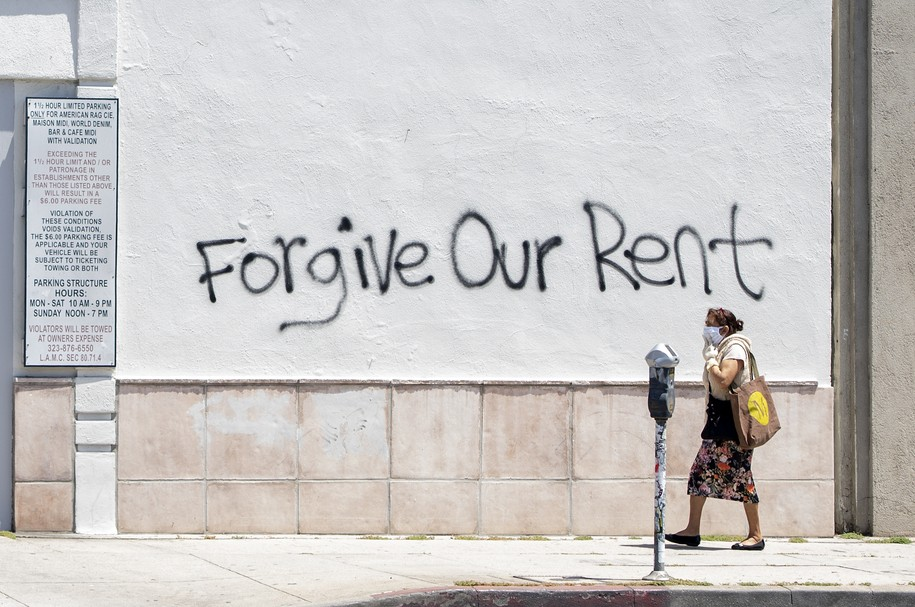 A woman wearing a mask walks past a wall bearing a graffiti asking for rent forgiveness on La Brea Ave on National May Day amid the Covid-19 pandemic,  May 1, 2020, in Los Angeles, California. - Several cities and states, including California, have passed executive orders prohibiting eviction of tenants affected by the coronavirus crisis..But when the lockdown lifts, the moratorium will end. And tenants will have to pay their back-rent or move out. (Photo by VALERIE MACON / AFP) (Photo by VALERIE MACON/AFP via Getty Images)