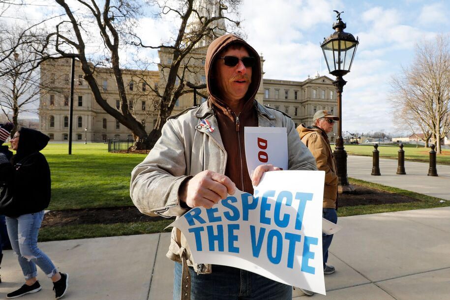 Matthew Shepard, a supporter of US President Donald Trump rips up an sign that says, Uphold Democracy outside the Michigan State Capital as as Michigan's Board of State Canvassers vote today to certify the 2020 election in Lansing, Michigan on November 23, 2020. (Photo by JEFF KOWALSKY / AFP) (Photo by JEFF KOWALSKY/AFP via Getty Images)