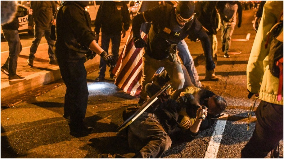 embers of the Proud Boys kick a member of Antifa on the ground during a protest on December 12, 2020 in Washington, DC.