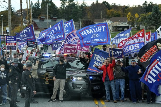 DALLAS, PA - OCTOBER 24: Supporters of President Donald Trump line the road as the motorcade for Democratic presidential nominee Joe Biden makes its way to a drive-in campaign rally at Dallas High School on October 24, 2020 in Dallas, Pennsylvania. Biden is making two campaign stops in the battleground state of Pennsylvania on Saturday. (Photo by Drew Angerer/Getty Images)