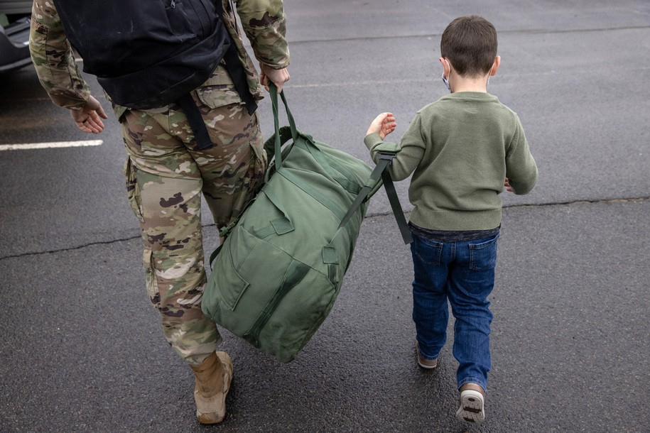 FORT DRUM, NEW YORK - DECEMBER 10: Cal Wasilewski, 5, helps his father U.S. Army Maj. Kurt Wasilewski carry his duffel after soldiers returned home from a 9-month deployment to Afghanistan on December 10, 2020 at Fort Drum, New York. The 10th Mountain Division soldiers who arrived this week are under orders to isolate at home or in barracks, finishing their quarantine just before Christmas. The troops were replaced in Afghanistan by a smaller force, as the U.S. military continues to reduce troop levels Afghanistan. (Photo by John Moore/Getty Images)