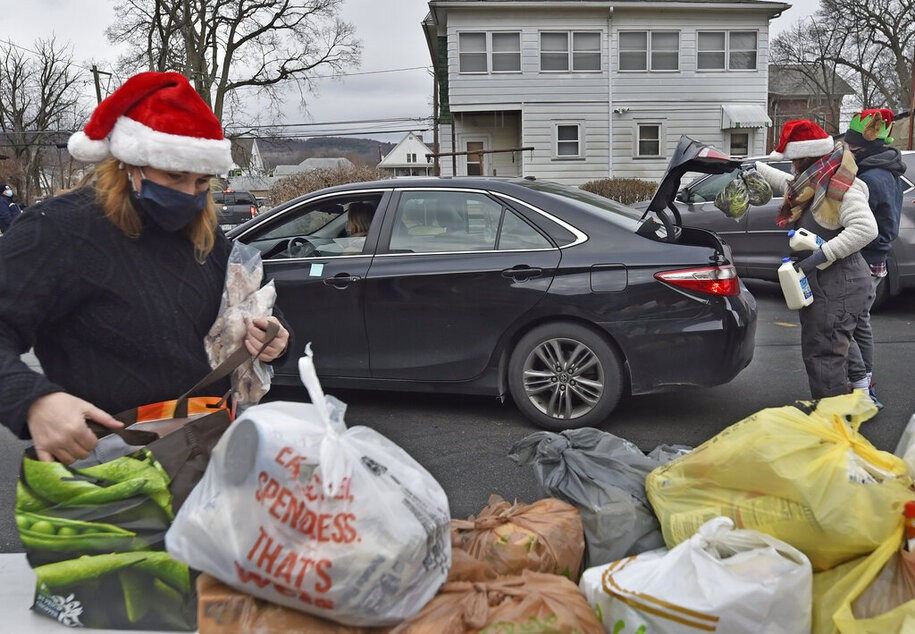 Volunteers fill cars with food at a drive thru food bank. Since the start of Covid the Al Beech food pantry has been very busy, today they served there one millionth guest. For Christmas volunteers wore Santa hats and handed out gift cards, candy and balloons along with the regular food goods. (Photo by Aimee Dilger / SOPA Images/Sipa USA)(Sipa via AP Images)