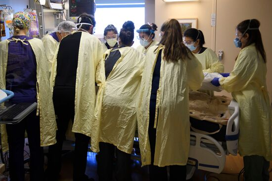 "A team of health care workers including physicians, nurses, certified nursing assistants, and respiratory specialists wear personal protective equipment (PPE) while turning a patient from their stomach onto their back in the Covid-19 intensive care unit (ICU) at Renown Regional Medical Center on December 16, 2020 in Reno, Nevada. - Renown Health converted two floors of a parking garage into an alternative care site for Covid-19 patients to increase hospital capacity amid a surge in cases, allowing other facilities to be used for patients in more serious condition. The site included the addition of flooring, electrical infrastructure, lighting, water, technology, sanitation, and ventilation. President Trump earlier this month retweeted a tweet that described Renown's structure as ""the fake Nevada parking garage hospital"" due to a lack of patients in the picture taken before the facility opened. The site is for patients that have mild to moderate Covid-19 cases and do not require critical care, with 24 patients currently and 350 patient visits to date. (Photo by Patrick T. Fallon / AFP) (Photo by PATRICK T. FALLON/AFP via Getty Images)"