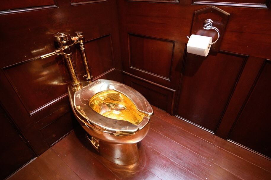 """Daily UK Life 2019  WOODSTOCK, ENGLAND - SEPTEMBER 12: """"America"""", a fully-working solid gold toilet, created by Maurizio Cattelan, is seen at Benheim Palace on September 12, 2019 in Woodstock, England. The artwork is still missing following what police believe to be a burglary on September 14, in which the toilet, valued by some at £4.8million, was taken. In 1996, Cattelan famously stole the entire contents of one of his own exhibitions in Amsterdam but has strongly denied any involvement with this latest theft. (Photo by Leon Neal/Getty Images)"""