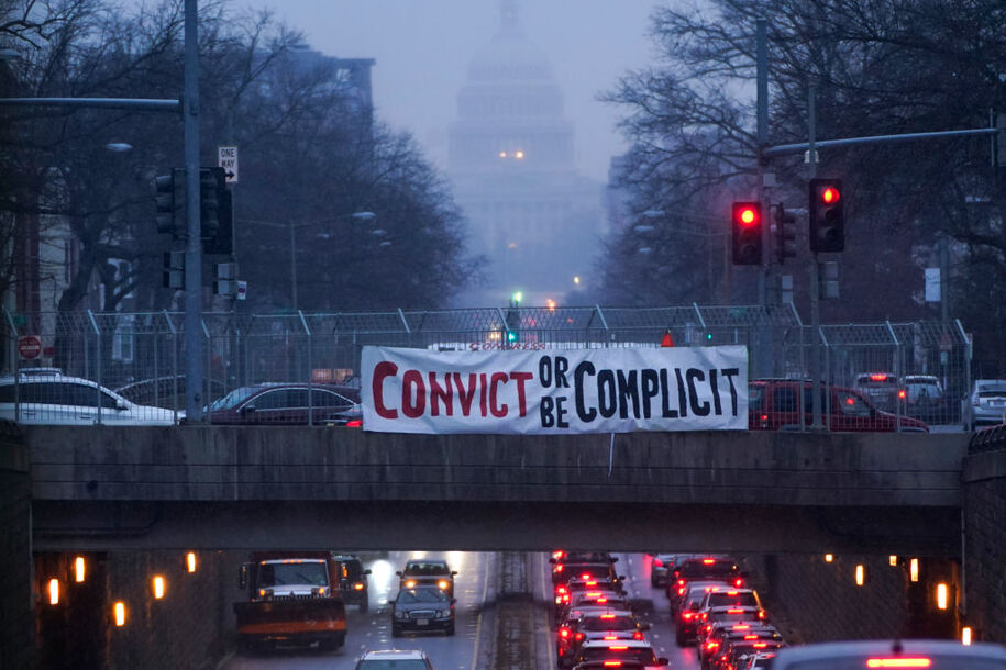 WASHINGTON, DC - February 10: A placard reading `` Condemned or be complicit '' hangs from a bridge on North Capitol Street on the second day of former President Donald Trump's second trial at the U.S. Capitol on February 10, 2021 in Washington, DC.  House impeachment administrators will prove that Trump was unilaterally responsible for the January 6 attack on the US Capitol, and that he should be condemned and barred from holding public office again.  (Photo by Drew Angerer / Getty Images)