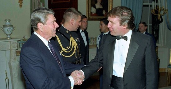 Former President Donald Trump is greeted by his ideological precursor President Ronald Reagan at a 1987 White House reception.