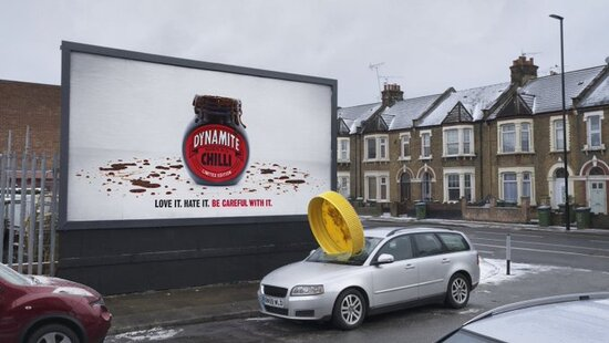 Marmite Dynamite, a new limited edition version of the spread with added chilli flavour, is being advertised with a series of billboards that see its lid blown off.... To promote the new variety, ad agency adam&eveDDB has created a series of dramatic billboards, which see the lid of the Marmite jar supposedly blown off by its powerful chilli flavouring. The first version, above, showed a lid appearing to explode out of a poster site and into a nearby car windscreen.  Follow up executions will feature huge lids blown skywards and hooked onto nearby buildings and trees. All posters feature a variation on the love it-hate it tagline, which reads: 'Love it, hate it, be careful with it.'