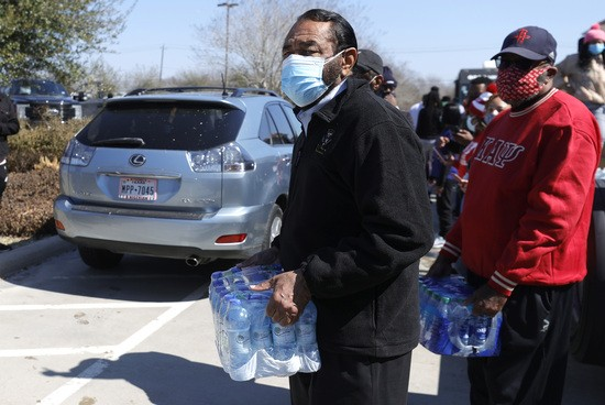 HOUSTON, TEXAS - FEBRUARY 20: U.S. Rep. Al Green (L) (D-TX) prepares to load a case of water into a car during a water distribution event at the Fountain Life Center on February 20, 2021 in Houston, Texas. Much of Texas is still struggling with historic cold weather, power outages and a shortage of potable water after winter storm Uri swept across 26 states with a mix of freezing temperatures and precipitation. Many Houston residents do not have drinkable water at their homes and are relying on city water giveaways. (Photo by Justin Sullivan/Getty Images)