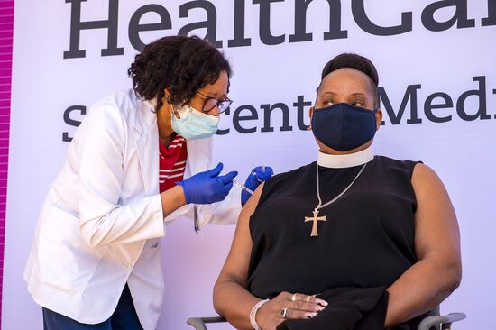 Pastor Brenda Barnes is vaccinated by nurse Marie St. Jean at Hartford HealthCare St. Vincents Medical Center in Bridgeport, Connecticut on February 26, 2021. - Nine local clergy members were given the Pfizer-BioNTech Covid-19 Vaccine, aiming to educate and inspire their parishioners and minority communities to get vaccinated. (Photo by Joseph Prezioso / AFP) (Photo by JOSEPH PREZIOSO/AFP via Getty Images)