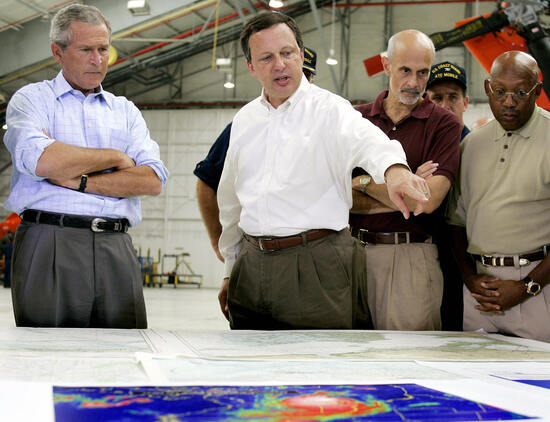 Mobile, UNITED STATES:  (FILES) US President George W. Bush (L) and Homeland Security Secretary Michael Chertoff (2nd R) get a briefing from Federal Emergency Management Agency (FEMA) chief Michael Brown (C) upon their arrival in this 02 September, 2005 file photo, at a US Coast Guard Base in Mobile, Alabama, before touring the devastation left by Hurricane Katrina. The head of the US Federal Emergency Agency (FEMA), much criticised over his handling of Hurricane Katrina, became the first political casualty of the crisis 09 September 2005, when he was replaced as pointman. FEMA director Michael Brown was to be recalled to Washington and replaced on the ground by Vice Admiral Thad Allen from the US Coastguard, Homeland Security Secretary Michael Chertoff said. Brown had faced calls to resign over the sluggish federal response to the disaster in which hundreds are feared to have died and billions of dollars' worth of damage sustained to property and infrastructure. AFP PHOTO/Jim WATSON  (Photo credit should read JIM WATSON/AFP via Getty Images)