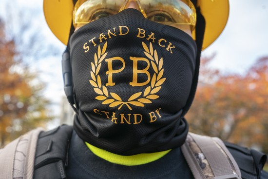 """SALEM, OR - NOVEMBER 07: A Proud Boy displays a bandana with the phrase Stand Back, Stand By, a reference to President Trumps statements about the group  during a """"Stop the Steal"""" rally on November 7, 2020 in Salem, Oregon. Angry supporters of President Trump took to the streets across the country following reporting that President-elect Joe Biden had won the election. (Photo by Nathan Howard/Getty Images)"""