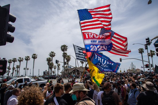 """HUNTINGTON BEACH, CA - APRIL 11: Protesters force an unidentified man carrying Trump and """"All Lives Matter"""" flags to walk away during a protest against white supremacy at Huntington Beach Pier on April 11, 2021 in Huntington Beach, California. The rally was organized by the Loyal White Knights and is believed to be part of a nationally coordinated group of white supremacist rallies in various cities across the nation. The Ku Klux Klan has been distributing flyers for the rally, and concerns in the Asian American and Pacific Islander communities are heightened as anti-Asian hate crimes have been rising since the start of the COVID-19 pandemic. (Photo by Apu Gomes/Getty Images)"""