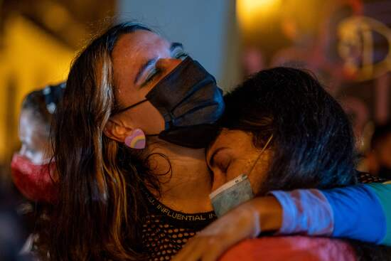 Two women hug as people led by the activist group, Feminist Collective, protest to demand Governor Wanda Vazquez to declare a state of emergency in response to recent gender based, femicides, assaults, and the disappearance of women in San Juan, Puerto Rico on September 28, 2020. (Photo by Ricardo ARDUENGO / AFP) (Photo by RICARDO ARDUENGO/AFP via Getty Images)