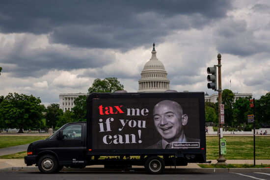 """WASHINGTON, DC - MAY 17: A mobile billboard calling for higher taxes on the ultra-wealthy depicts an image of billionaire businessman Jeff Bezos, near the U.S. Capitol on May 17, 2021 in Washington, DC. Organized by the group """"Patriotic Millionaires,"""" the mobile billboards are rolling through Washington, DC and New York City on Monday to mark Tax Day, calling for higher taxes for wealthy Americans. (Photo by Drew Angerer/Getty Images)"""