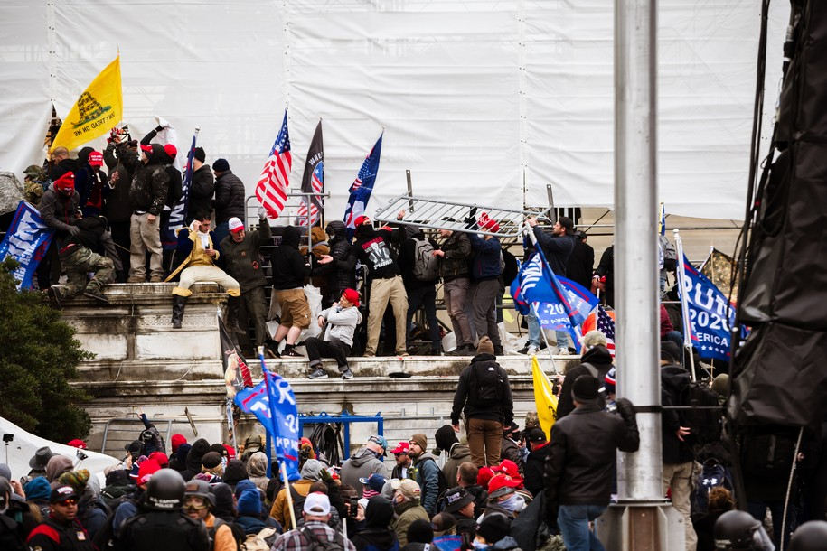 WASHINGTON, DC - JANUARY 06: A group of pro-Trump protesters climb the walls of the Capitol Building after storming the West lawn on January 6, 2021 in Washington, DC. A pro-Trump mob stormed the Capitol, breaking windows and clashing with police officers. Trump supporters gathered in the nation's capital today to protest the ratification of President-elect Joe Biden's Electoral College victory over President Trump in the 2020 election. (Photo by Jon Cherry/Getty Images)