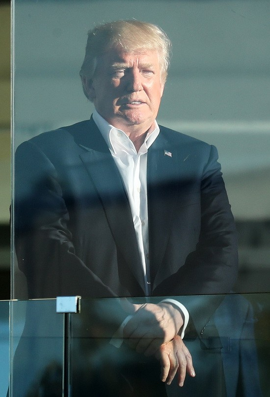 JERSEY CITY, NJ - OCTOBER 01:  U.S. President Donald Trump looks on from the clubhouse during Sunday singles matches of the Presidents Cup at Liberty National Golf Club on October 1, 2017 in Jersey City, New Jersey.  (Photo by Rob Carr/Getty Images)