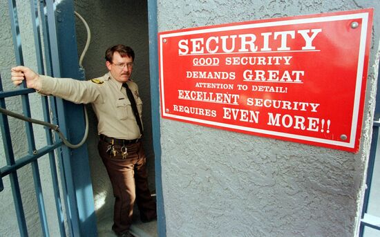 """FLORENCE, AZ - FEBRUARY 11:  Correctional Officer Jim Robideau holds the gate open 11 February to the main prison complex which houses the """"Death House"""" in Florence, some 80 miles (128 km) southeast of Phoenix, Arizona.  The state is scheduling a total of 11 executions for 1999. The state currently has 119 inmates under sentence of death, 114 of which reside at the Special Management Unit II also located in Florence. The Death House consists of a lethal injection room and a gas chamber used for executions. Two German brothers, Karl and Walter LaGrand, are held in this prison complex and are scheduled to be executed by lethal gas 24 February  and 03 March respectively for the 1982 murder of a 63-year-old bank manager during a hold-up in Marana, AZ. The brothers would be the first Germans to be executed on US soil since World War II. Karl LaGrand would be the 15th inmate executed in Arizona since the reinstatement of death penalty in 1992, and the third inmate executed in 1999. AFP PHOTO  Mike FIALA/msf  (Photo credit should read MIKE FIALA/AFP via Getty Images)"""