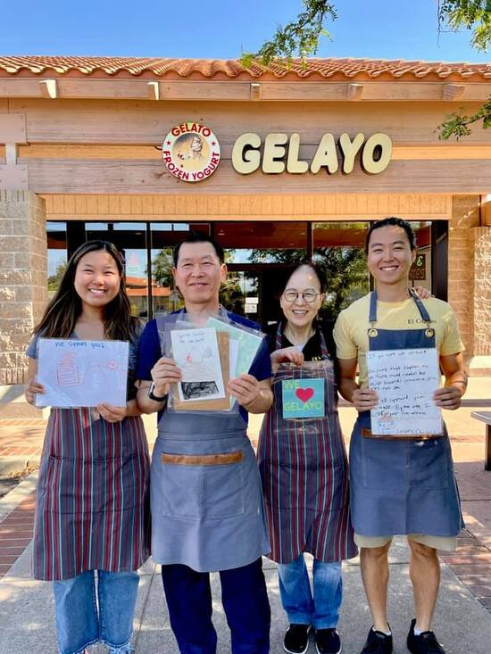 A family of four Asian Americans stand in front of their yoghurt shop, Gelayo, showing the letters and cards of support they've received.