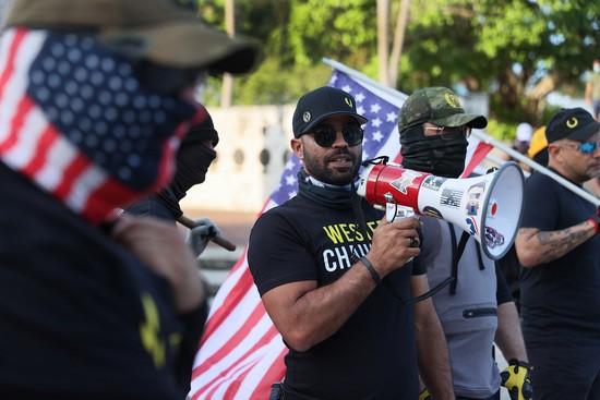 MIAMI, FLORIDE - 25 MAI: Enrique Tarrio (C), chef des Proud Boys, utilise un mégaphone tout en contre-manifestant des personnes rassemblées au Torch of Friendship pour commémorer le premier anniversaire du meurtre de George Floyd le 25 mai 2021 à Miami, en Floride.  M. Tarrio a dirigé un groupe dans la région pour exprimer son soutien aux policiers.  Le meurtre de Floyd par le policier de Minneapolis Derek Chauvin a déclenché une protestation mondiale et continue de stimuler le mouvement Black Lives Matter.  (Photo de Joe Raedle/Getty Images)