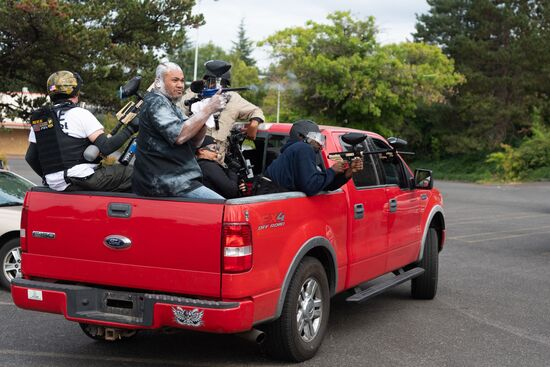 Members of the Proud Boys shoot paintballs out of the back of a truck during an altercation with anti-fascist activists following a far-right rally on August 22, 2021 in Portland, Oregon. - Far-right groups, including the Proud Boys held a rally in Portland on the anniversary of a violent altercation with anti-fascist activist a year earlier. (Photo by Mathieu Lewis-Rolland / AFP) (Photo by MATHIEU LEWIS-ROLLAND/AFP via Getty Images)