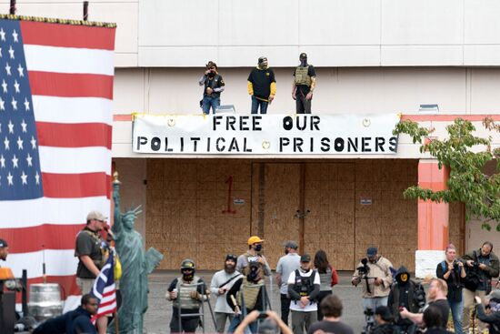 Members of the Proud Boys stand above a sign during a far-right rally in Portland, Oregon on August 22, 2021. - Far-right groups, including the Proud Boys held a rally in Portland on the anniversary of a violent altercation with anti-fascist activist a year earlier. (Photo by Mathieu Lewis-Rolland / AFP) (Photo by MATHIEU LEWIS-ROLLAND/AFP via Getty Images)