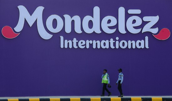 Indian workers stand in front of a signboard during the opening of the Mondelez International facility in Sri City in the Indian state of Andhra Pradesh on 25 April, 2016...The facility will produce approximately 60,000 tons of Cadbury Dairy Milk chocolate annually. / AFP / ARUN SANKAR        (Photo credit should read ARUN SANKAR/AFP via Getty Images)