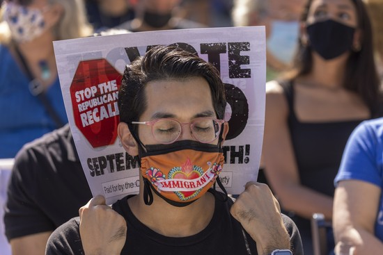 """CULVER CITY, CA - SEPTEMBER 04: A man wearing an """"immigrant"""" face mask uses a rally sign as shade against the heat while he awaits the start of a """"Stop the Republican Recall"""" rally where Sen. Elizabeth Warren, D-Massachusetts, would campaign for Gov. Gavin Newsom at Culver City High School on September 4, 2021 in Culver City, California. Forty-six candidates, mostly Republicans, are running to overthrow the governor in this years special recall election on September 14, ahead of next years regularly scheduled gubernatorial vote. (Photo by David McNew/Getty Images)"""