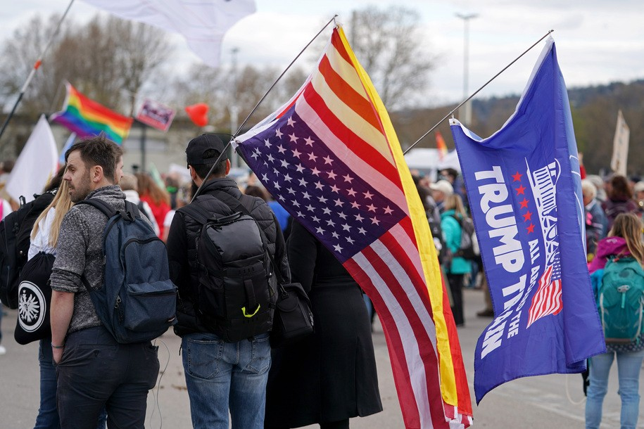 """STUTTGART, GERMANY - APRIL 03: Supporters of the Querdenken movement carry US and Trump flags as they march for what they claim are their basic rights during the third wave of the coronavirus pandemic on April 03, 2021 in Stuttgart, Germany. Querdenken, which means """"lateral thinking"""" is Germany's biggest movement that to protest against coronavirus-related lockdown measures. Querdenken encompasses a wide range of supporters, including average citizens, mystics, hippies, religious fundamentalists, conspiracy theorists and neo-Nazis. Germany is in the midst of its third wave of the pandemic brought on by the rapid spread of the B117 variant. (Photo by Thomas Niedermueller/Getty Images)"""