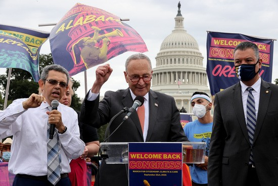 WASHINGTON, DC - SEPTEMBER 21: Senate Majority Leader Charles Schumer (D-NY) (C) addresses thousands of demonstrators from across the country with Sen. Alex Padilla (D-CA) (R) as they rally in support of a pathway to citizenship for the more than 11 million undocumented immigrants living in the United States on the National Mall on September 21, 2021 in Washington, DC. Activists, union leaders, organizers and political leaders addressed the marchers as they rallied outside the headquarters of the U.S. Immigration and Customs Enforcement and the U.S. Capitol. (Photo by Chip Somodevilla/Getty Images)