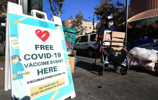A man pushes his belongings past a sign announcing a free Covid-19 vaccination clinic for homeless people in Los Angeles, California on September 22, 2021, hosted by the Los Angeles County Department of Public Health and United Way. - Covid-related hospitalizations across Los Angeles County fell below 1,000 for the first time since late-July as a steady decline continues from a mid-August peak of nearly 1,800. (Photo by Frederic J. BROWN / AFP) (Photo by FREDERIC J. BROWN/AFP via Getty Images)