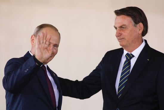 Russia's President Vladimir Putin (L) waves as he arrives to the 11th BRICS Summit next to Brazil's President Jair Bolsonaro (R) on November 14, 2019 in Brasilia, Brazil. - Brazil's President Jair Bolsonaro walked a diplomatic tightrope, as he seeks to boost ties with Beijing and avoid upsetting key ally Donald Trump, on the eve of a summit with their BRICS counterparts from Russia, India and South Africa. (Photo by Sergio LIMA / AFP) (Photo by SERGIO LIMA/AFP via Getty Images)